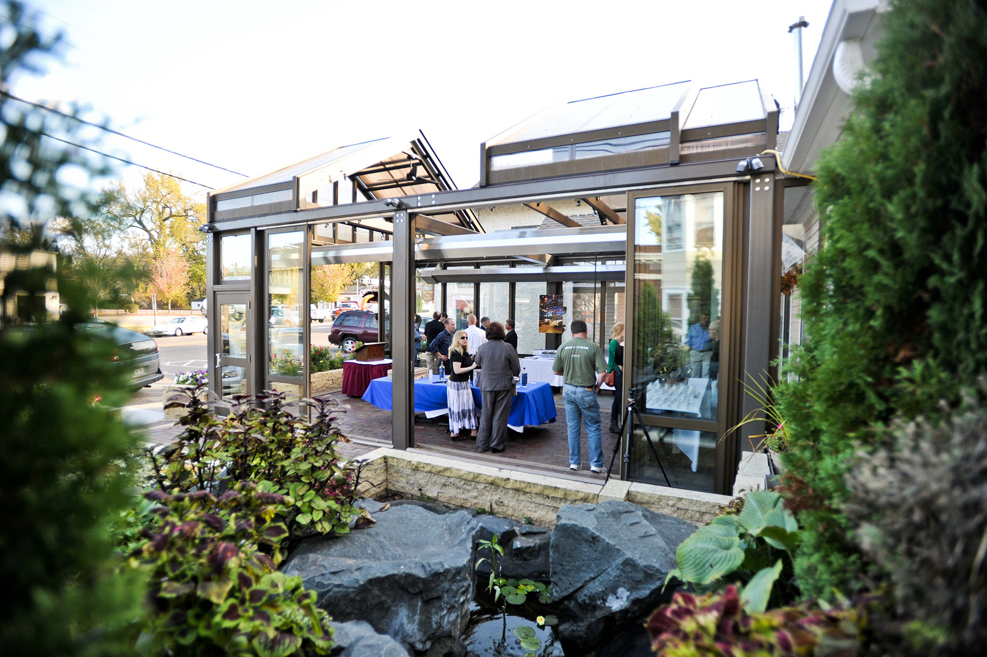 Restaurant patio structure with retractable roof and opening walls