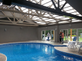 Swimming pool with opening roof