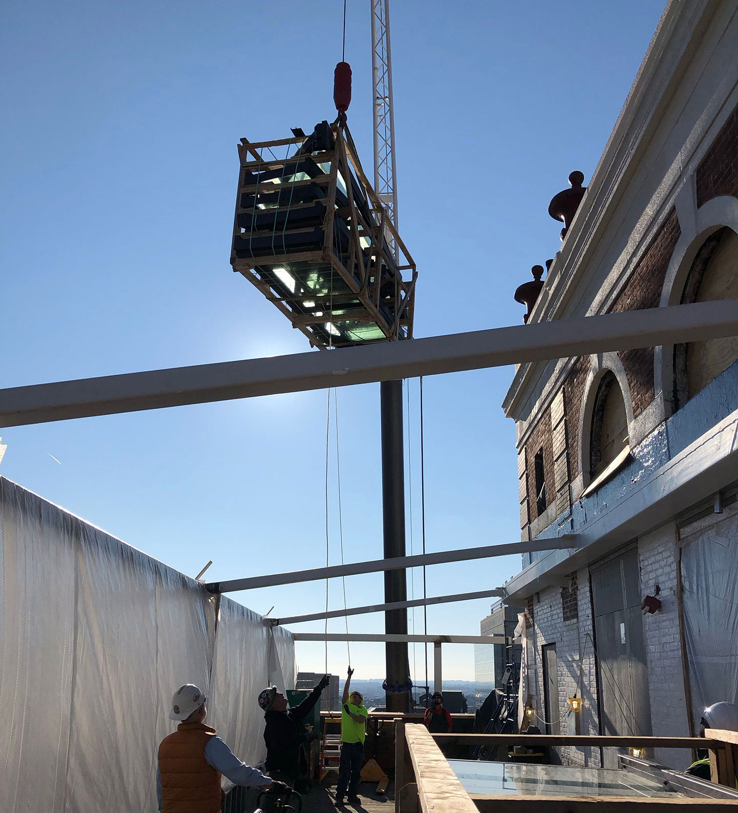 Retractable patio structure being installed on rooftop patio